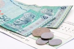 Деньги малайзийского ринггита na górze проверки на белой предпосылке Стоковое фото RF