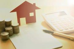 Деньги, монетка кучи с книгой сбережений и дом бумаги, концепция стоковое фото