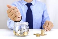 Деньги молодого человека депозируя в стеклянном опарнике стоковое фото rf