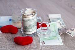 Деньги около красных сердец Доллары в открытом опарнике с евро на серой деревянной предпосылке скопируйте космос Любовь вектор Ва Стоковые Фото