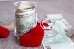 Деньги около красных сердец Доллары в открытом опарнике с евро на серой деревянной предпосылке скопируйте космос Любовь вектор Ва Стоковые Изображения