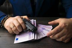 Деньги, оружия демонстрируя концепцию бандита Террористическая деятельность стоковое фото rf