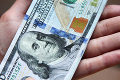 Деньги долларовых банкнот США в руке Стоковое Изображение RF