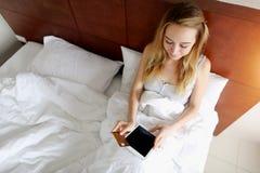 Деньги переноса молодой женщины держат кредитную карточку и таблетку дебита кладя в белую кровать дома с солнечностью Стоковая Фотография
