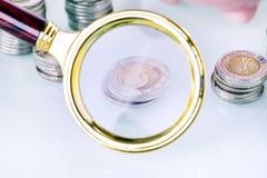 Деньги под loupe Сигнал на домашних финансах Стоковые Фото