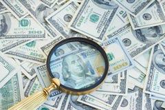 Деньги под manifying стеклом Стоковая Фотография RF