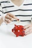 Деньги сбережений женщины с красной копилкой Стоковые Изображения RF