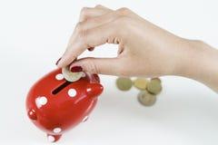 Деньги сбережений женщины с красной копилкой Стоковое фото RF