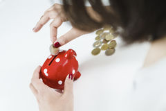 Деньги сбережений женщины с красной копилкой Стоковая Фотография