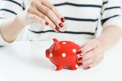 Деньги сбережений женщины с красной копилкой Стоковое Фото