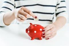 Деньги сбережений женщины с красной копилкой Стоковая Фотография RF