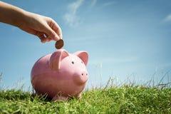 Деньги сбережений руки ребенка в копилке Стоковая Фотография RF