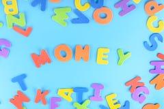 Деньги слова заработаны пестротканых писем Яркая надпись на голубой предпосылке Стоковая Фотография