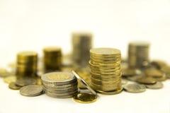 Деньги, стог монеток на белой предпосылке чеканит сбережениа кучи дег рук принципиальной схемы защищая расти дела Доверие в будущ Стоковое Изображение RF