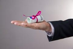 Деньги с лентой в мужской руке на серой предпосылке Стоковое фото RF