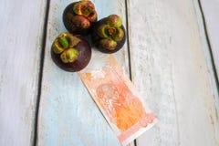 Деньги с плодоовощ мангустана Стоковое Фото