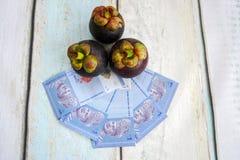 Деньги с плодоовощ мангустана Стоковые Изображения RF