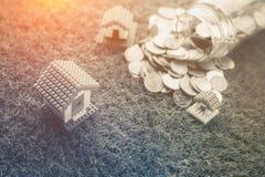 Деньги чеканят разливать из стеклянной модели бутылки и дома Стоковое Фото