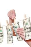 Деньги щипка руки на изолированной бельевой веревке Стоковая Фотография
