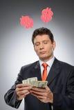 Деньг-создатель. Смешной бизнесмен с hornes доллара на голове Стоковое Фото