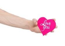 День валентинки и тема влюбленности: рука держит поздравительную открытку в форме розового сердца с словами любит вас изолировала Стоковые Изображения RF