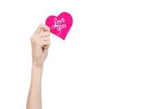 День валентинки и тема влюбленности: рука держит поздравительную открытку в форме розового сердца с словами любит вас изолировала Стоковое фото RF
