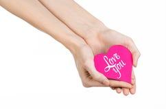 День валентинки и тема влюбленности: рука держит поздравительную открытку в форме розового сердца с словами любит вас изолировала Стоковые Изображения