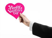 День валентинки и тема влюбленности: рука человека в черном костюме держа карточку в форме розового сердца Стоковое Изображение