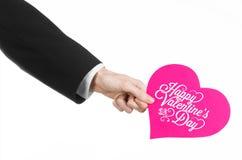 День валентинки и тема влюбленности: рука человека в черном костюме держа карточку в форме розового сердца Стоковые Фото