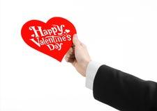День валентинки и тема влюбленности: рука человека в черном костюме держа карточку в форме красного сердца Стоковое Фото