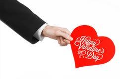 День валентинки и тема влюбленности: рука человека в черном костюме держа карточку в форме красного сердца Стоковое Изображение