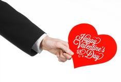 День валентинки и тема влюбленности: рука человека в черном костюме держа карточку в форме красного сердца Стоковое фото RF