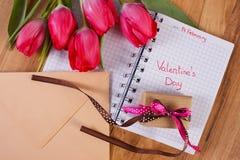 День валентинок написанный в тетради, свежих тюльпанах, любовном письме и подарке, украшении для валентинок Стоковое Изображение RF
