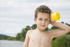 День лета яркий солнечный курчавый мальчик стоит на пляже около r Стоковое Фото