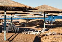 День на зонтиках соломы пляжа и loungers солнца Стоковые Фото