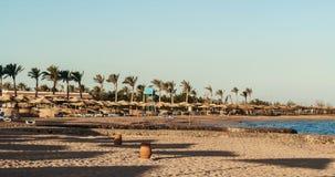 День на зонтиках соломы пляжа и loungers солнца Стоковые Изображения