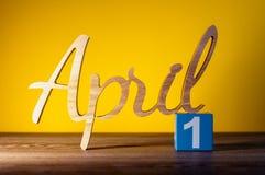 День 1 1-ое апреля месяца, ежедневный деревянный календарь на таблице и предпосылка апельсина Концепция времени весны Стоковая Фотография