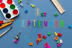 День 1 1-ое сентября месяца, назад к концепции школы Календарь на предпосылке рабочего места учителя или студента с школой Стоковые Фотографии RF