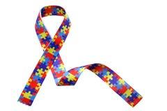 День осведомленности и гордости аутизма мира с головоломкой делает по образцу ленту изолированную на белизне Стоковое фото RF