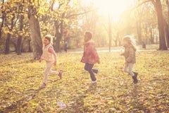 День осени в парке девушка мальчика влюбленнаяся дет смотрит усмешки парка Стоковое фото RF