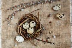 День пасхи Небольшое гнездо с яйцами триперсток на предпосылке дерюги, текстуре мешковины стоковое фото