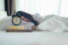 День раннего творчества Часы близкого поднимающего вверх сигнала тревоги винтажные с женщинами спят кровать в утре стоковые изображения