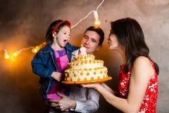 День рождения детей праздника семьи темы и дуть вне свечи на большом торте молодые люди семьи из трех человек стоя и держа 5 Стоковое фото RF