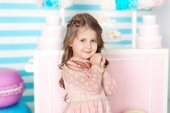 День рождения и концепция счастья - счастливая маленькая девочка с помадками на предпосылке шоколадного батончика Портрет красиво стоковое изображение