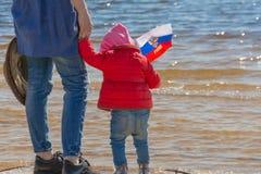 День России E Счастливый ребенк, милая девушка маленького ребенка с флагом России Мама с ребенком морем стоковое фото