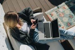 день солнечный над взглядом Молодая коммерсантка сидит на белом кресле на террасе, используя компьтер-книжку и smartphone стоковая фотография rf