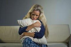 депрессия и боль отжатой и тревоженой красивой белокурой женщины 40s страдая чувствуя расстроенное кресло унылое a софы усаживани стоковые изображения rf