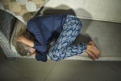 депрессия и головная боль отжатой и тревоженой красивой белокурой женщины 40s страдая чувствуя расстроенный плакать унылый дома в стоковое фото