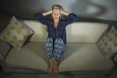 депрессия и головная боль отжатой и тревоженой красивой белокурой женщины 40s страдая чувствуя расстроенное кресло s софы усажива стоковое фото