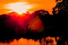 Дерева силуэта ландшафта захода солнца и света справедливо река воды красивого красочного рефлекторное во времени сумерк неба Стоковая Фотография RF